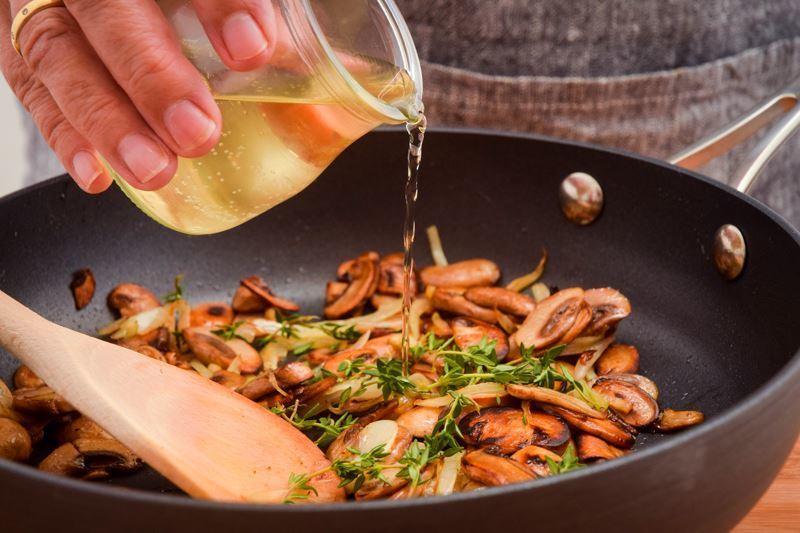 Woman adding white wine to a pan of sauteed mushrooms with onion and thyme.