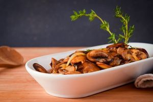Sauteed mushrooms with thyme twigs in a porcelain dish on wooden counter.