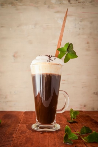 Irish Coffee with a four-leaf clover on light brown background.