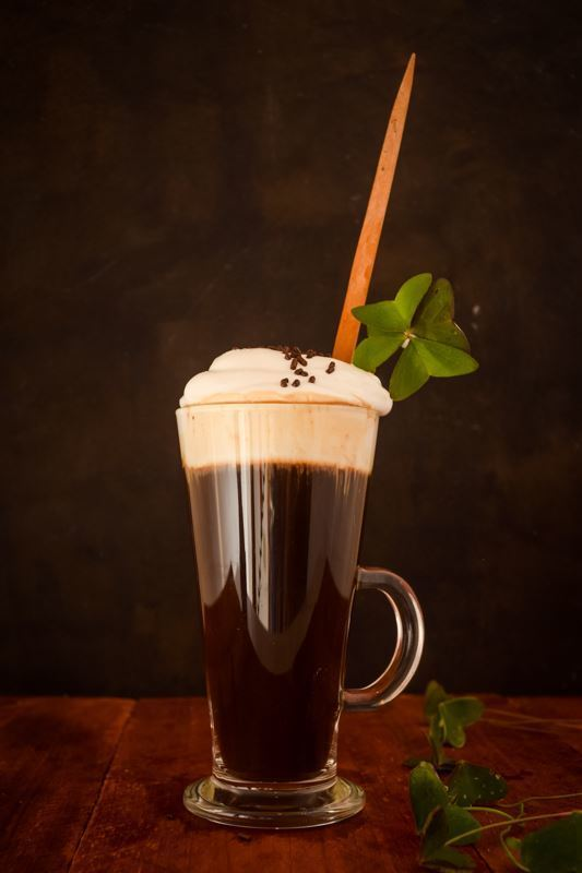 Irish Coffee with a four-leaf clover on brown background.