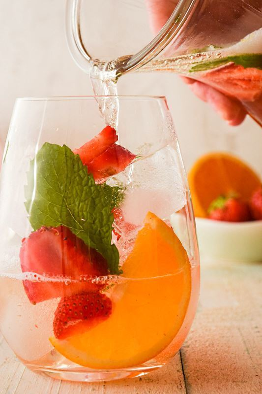 Wine glass filled with fruit and ice, white wine pouring in from a glass jug.