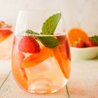 Wine glass filled with white wine sangria and mint leaves.