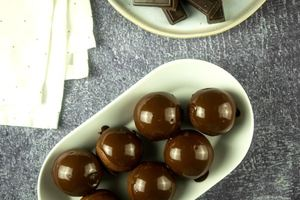 Chocolate covered donut holes on a white serving dish.
