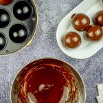 Cake pop maker, bowl of melted chocolate coating and dish of chocolate covered donut holes.