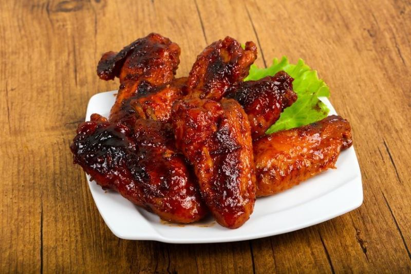 Caramelized Chicken Wings on a plate on wooden background.