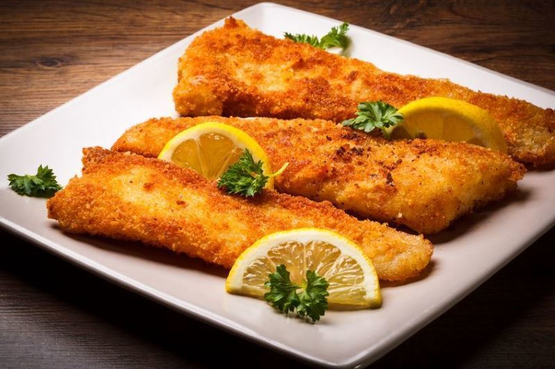 Crispy Fried Fish with Cornmeal and lemon slices on a plate.
