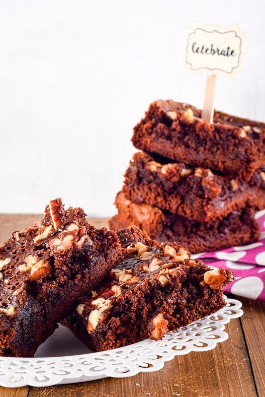Stacked brownies on a wooden table and polka dot napkins. A popsicle stick in the top brownie with a note saying celebrate.