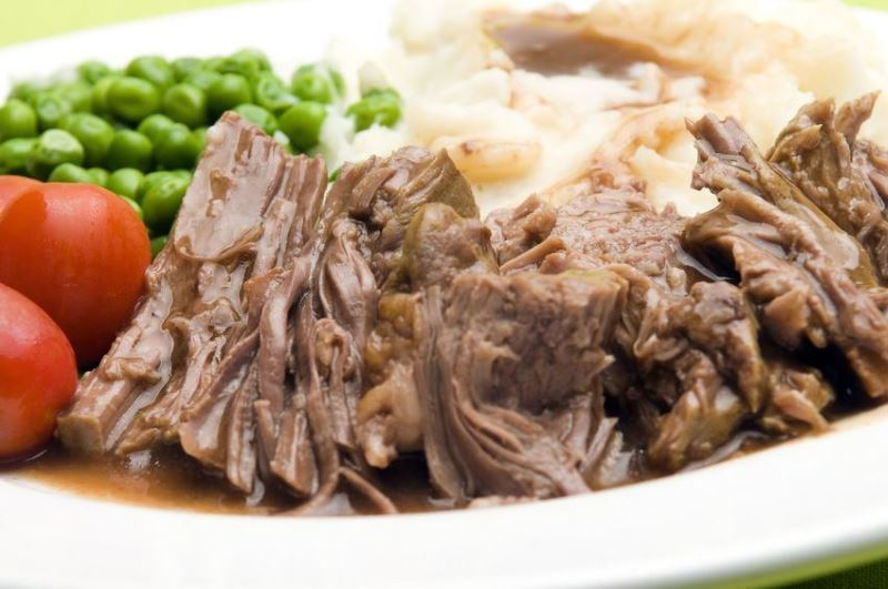Electric Skillet Chuck Roast with Onions and peas on a plate.