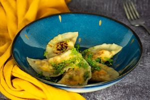 Freshly cooked pierogies on a beautiful blue Portuguese plate, yellow kitchen cloth underneath.