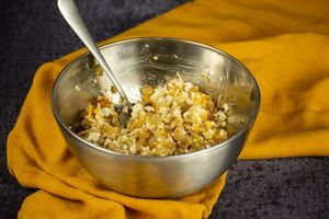 Cheeses, spices, potato and onions in a bowl mixed together, yellow dish cloth underneath.