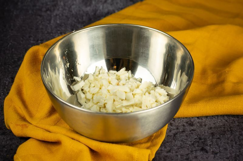 Cheese chunks in a bowl, yellow dish cloth underneath.