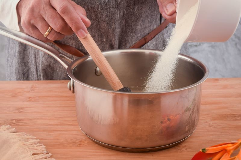 Woman's hand pouring sugar into a pot and mixing with water.