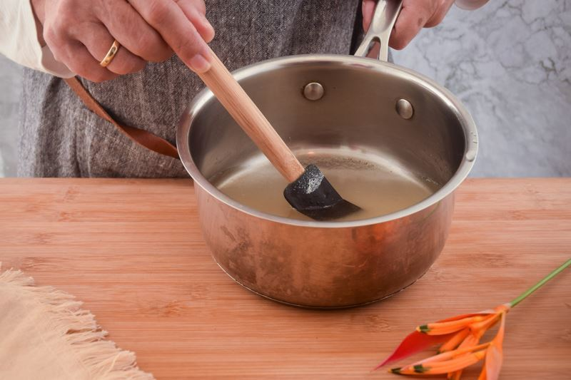Woman's hand mixing a sugar and water mixture in a pot.