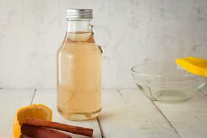 A glass bottle of simple syrup, cinnamon and orange on the side.