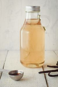 A glass bottle of simple syrup, vanilla beans on the side.