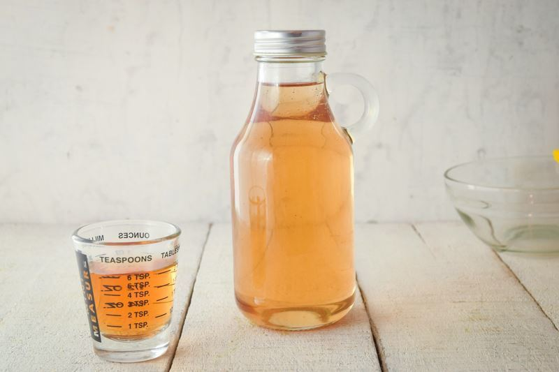 A glass bottle of simple syrup, a small measuring glass on the side.