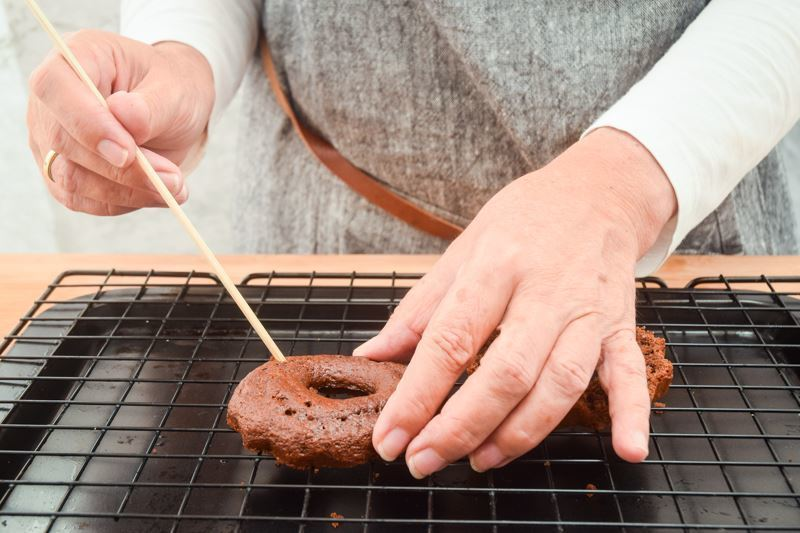 A small chocolate cake sliced in half, woman poking holes into them with a wooden skewer.