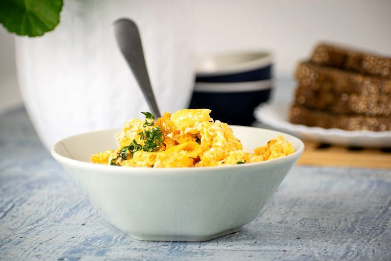 A pot of scrambled eggs with kimchi and kale with a fork in it.