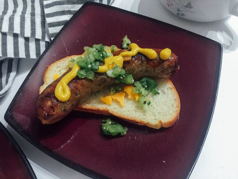 Bratwurst sausages with tomatillo relish on a slice of bread on a plate.