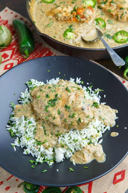 Creamy salsa verde skillet chicken over rice on a black plate.
