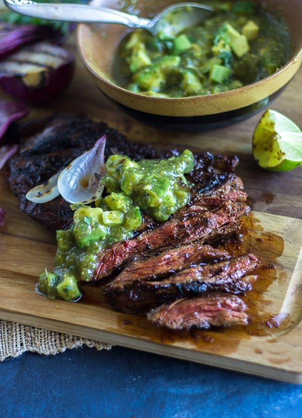 Grilled skirt steak with tomatillo avocado salsa on a wooden cutting board.