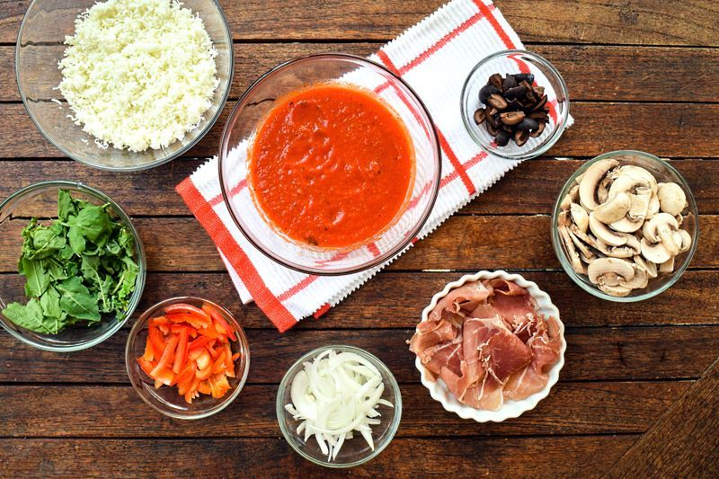How to grill pizza - prepped ingredients on wood background.