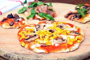 Grilled pizza on a wooden, circular cutting board.