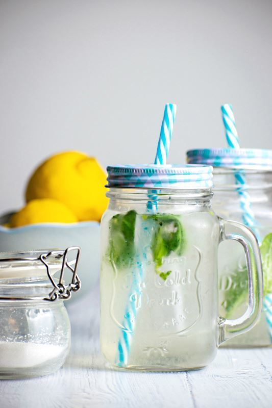 Decorative mason jars with lemonade and basil.