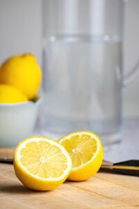 A pitcher of water and a lemon cut in half.