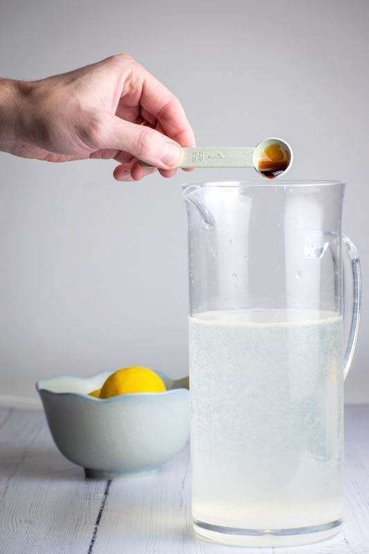 A tall pitcher of lemonade, a woman's hand pouring vanilla in.