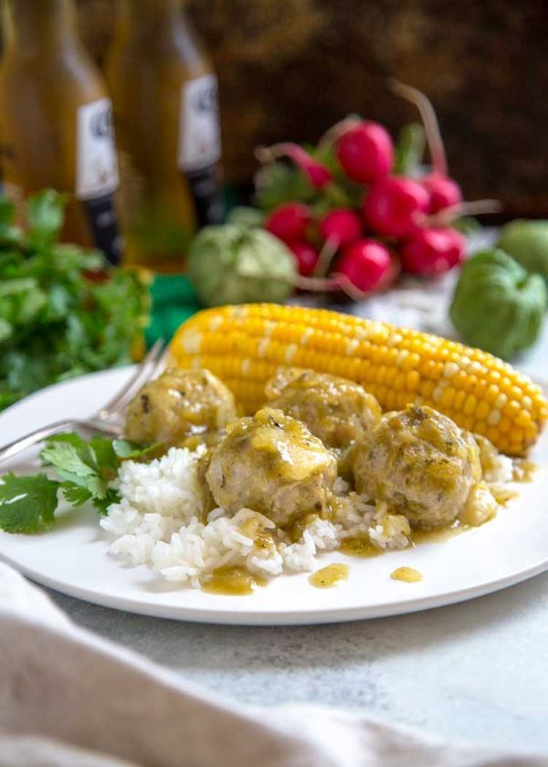 Stuffed Green Chili Meatballs on a plate with corn on the cob and rice.