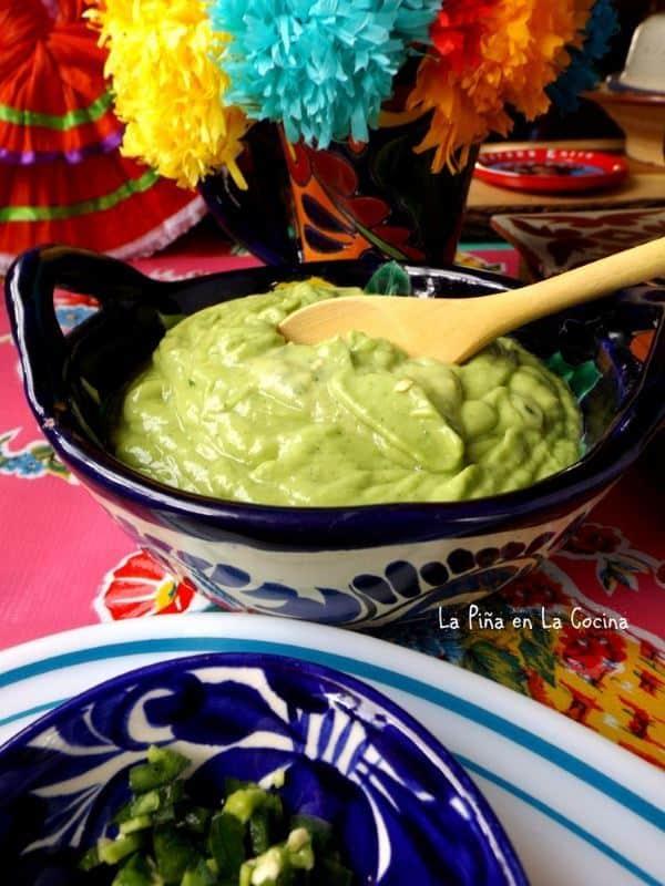 Tomatillo avocado salsa in a porcelain dish, bright multi-colored background.