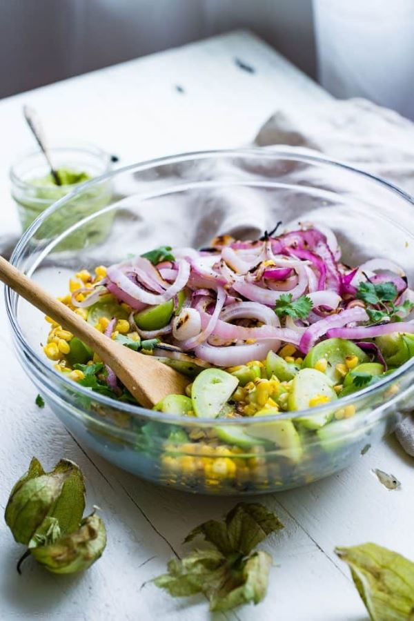 grilled corn salad with tomatillo in a clear glass bowl.