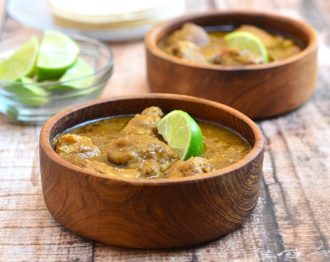 Pork chili verde in 2 wooden bowls with lime slice garnishes.