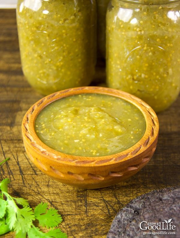 A wooden bowl of tomatillo salsa and 2 canning jars in the back.