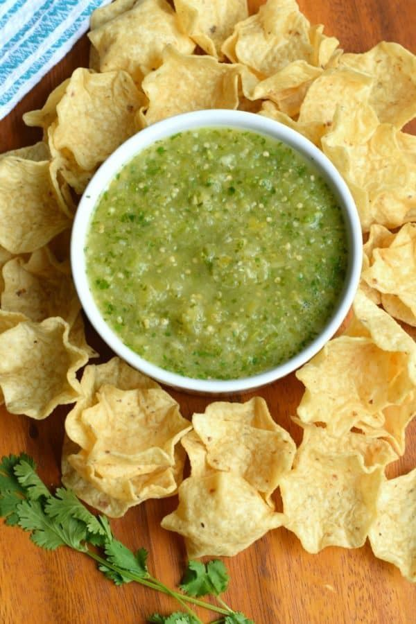 Mexican tomatillo salsa surrounded by tortillas.