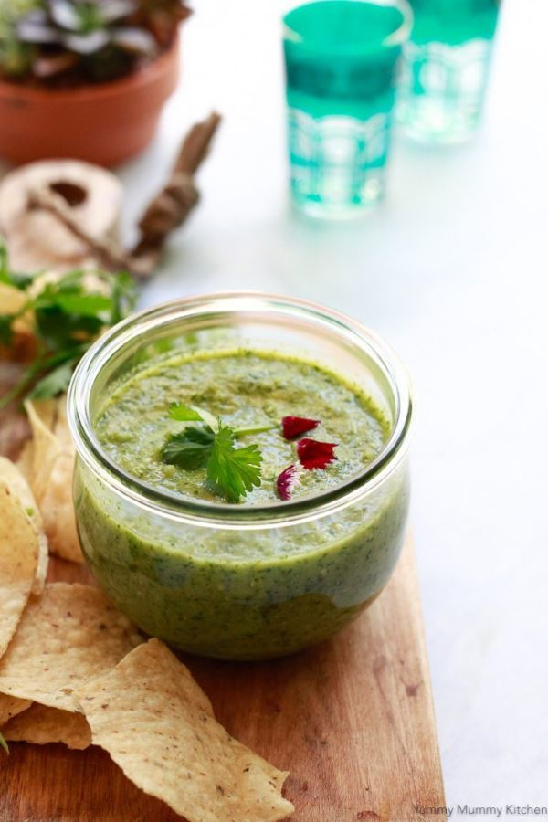 Tomatillo Salsa Verde in a small jar with tortilla chips on the side.