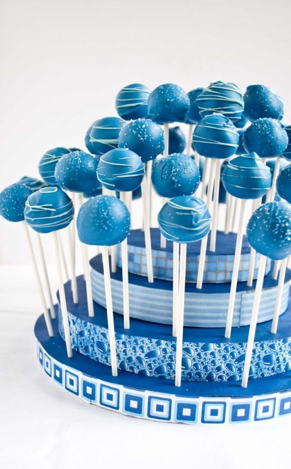 Baby boy shower blue cake pops on a blue stand.