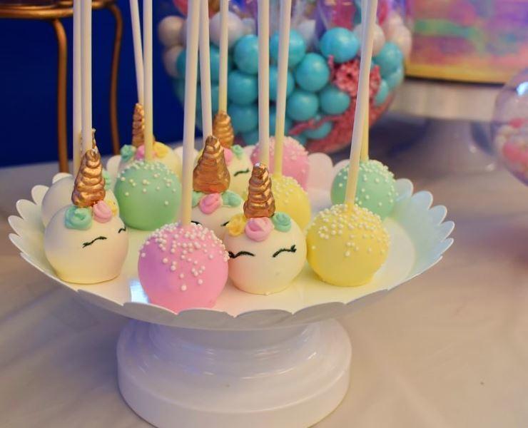 Unicorn cake pops on a white tray.