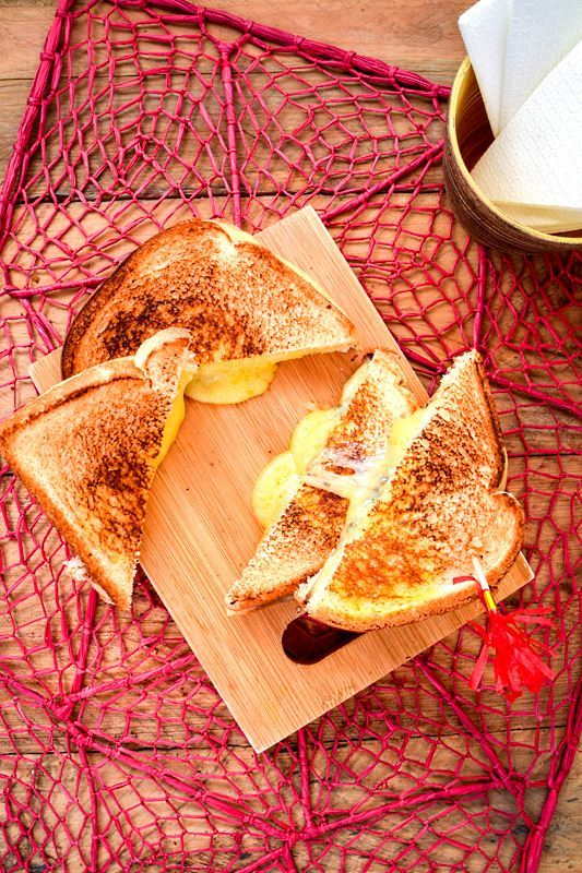 Electric skillet grilled cheese sandwiches on a cutting board. over a pink doiley.