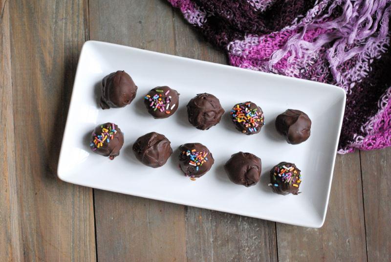 Chocolate gluten free cake balls on a white rectangular dish.