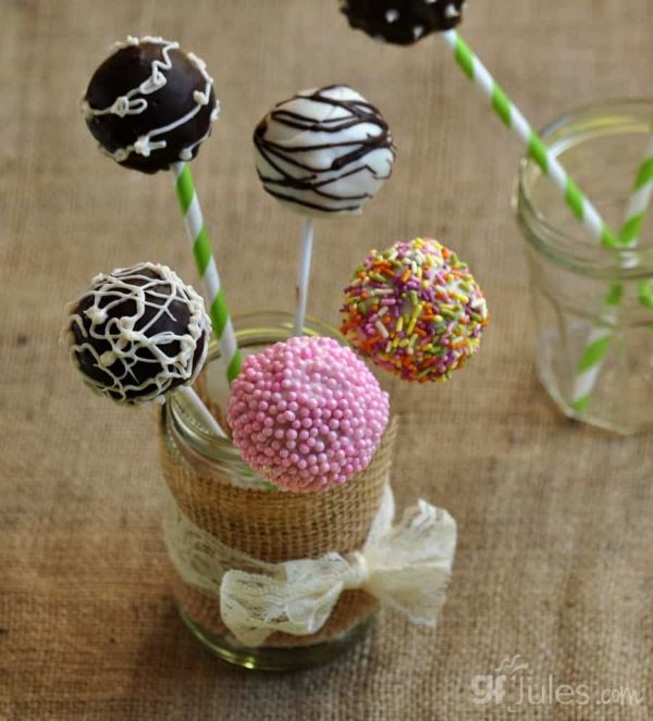 Gluten free cake pops in stand, frosted in sprinkled in different colors.
