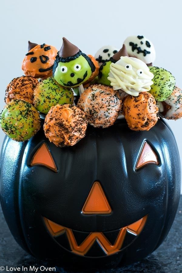 Witch, ghost and green and orange cake pops for Halloween in a black plastic jack o lantern.