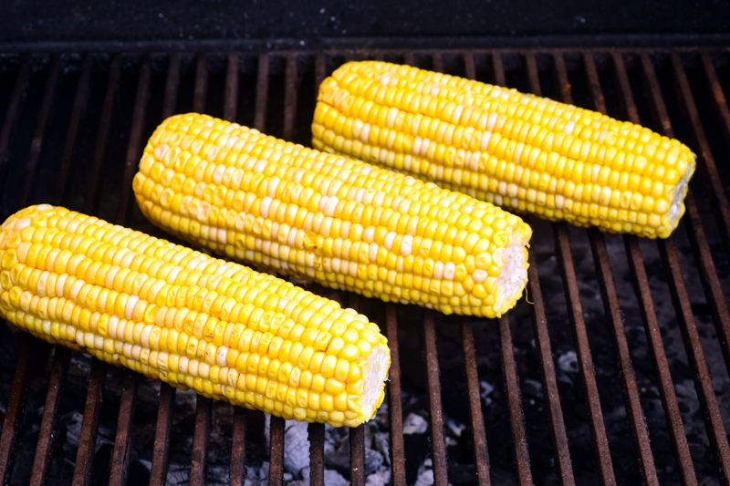 Cobs of corn on the grill.