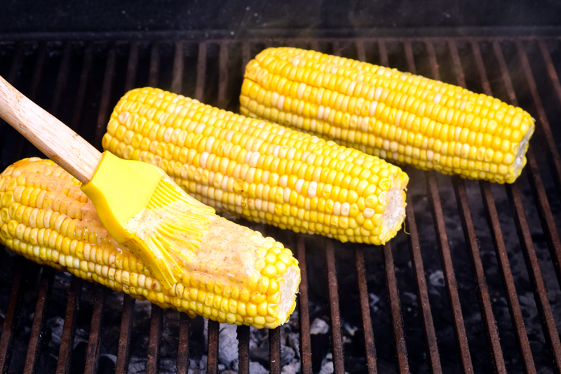 Cobs of corn grilling on the BBQ, one cob being brushed with Mexican seasoned butter.