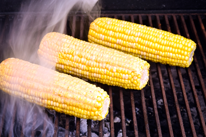 Cobs of corn grilling on the BBQ.
