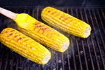Grilled corn cobs being brushed with butter.