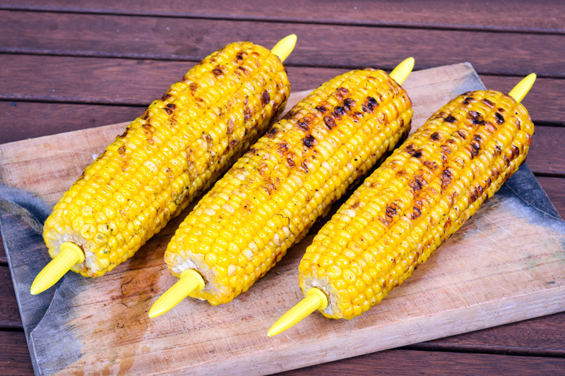 Grilled corn cobs on wooden background.