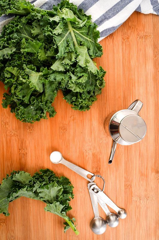 Kale and a wooden counter top, with measuring spoons and an oil can.