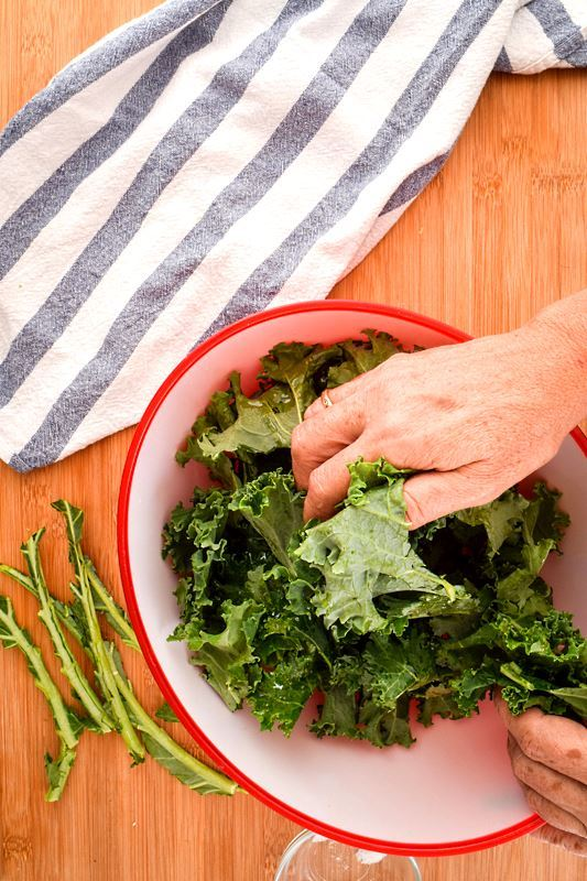 Kale chips in a bowl, a hand picking some up.